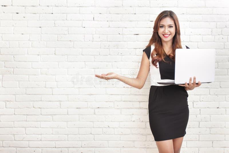 Όμορφη γυναίκα που κρατά ένα lap-top παρουσιάζοντας ένα διάστημα αντιγράφων στοκ φωτογραφίες με δικαίωμα ελεύθερης χρήσης