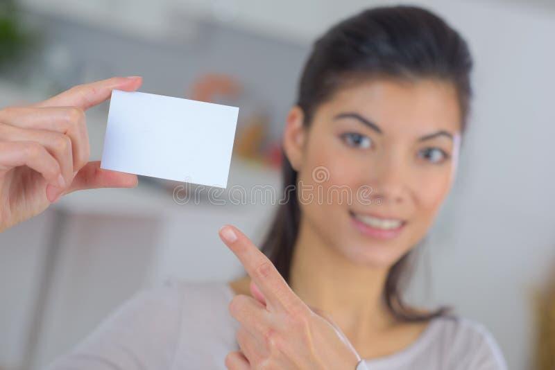 Όμορφη γυναίκα που κρατά και που παρουσιάζει κενή επαγγελματική κάρτα στοκ φωτογραφίες με δικαίωμα ελεύθερης χρήσης