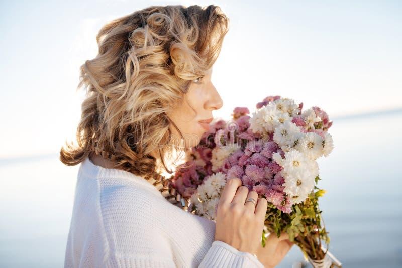 Όμορφη γυναίκα που κρατά μια δέσμη των άσπρων και ιωδών λουλουδιών στοκ εικόνες