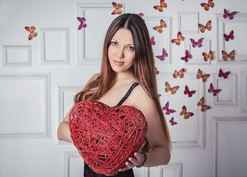 Όμορφη γυναίκα που κρατά τη με ιτιές καρδιά στοκ εικόνα
