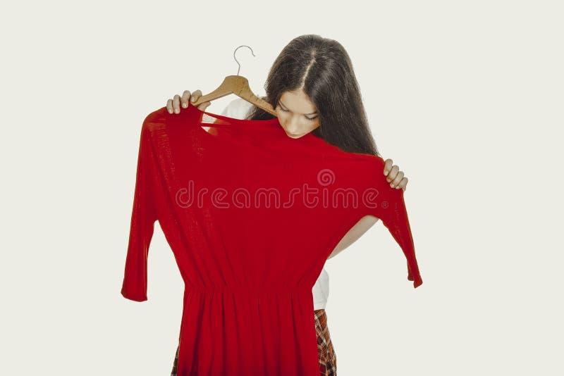 Όμορφη γυναίκα που κρατά το κόκκινο φόρεμα στοκ φωτογραφία με δικαίωμα ελεύθερης χρήσης