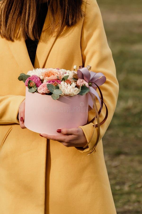 Όμορφη γυναίκα που κρατά το ρόδινο κιβώτιο με τα λουλούδια Δώρο στην ημέρα των γυναικών Floral σχέδιο αντιπροσωπείας, κείμενο θέσ στοκ εικόνα