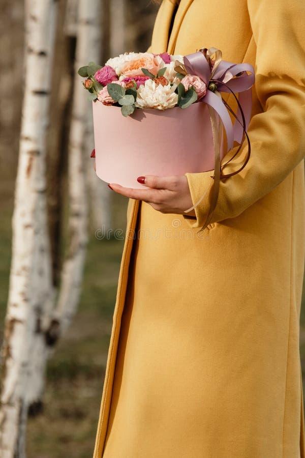Όμορφη γυναίκα που κρατά το ρόδινο κιβώτιο με τα λουλούδια Δώρο στην ημέρα των γυναικών Floral σχέδιο αντιπροσωπείας, κείμενο θέσ στοκ φωτογραφίες