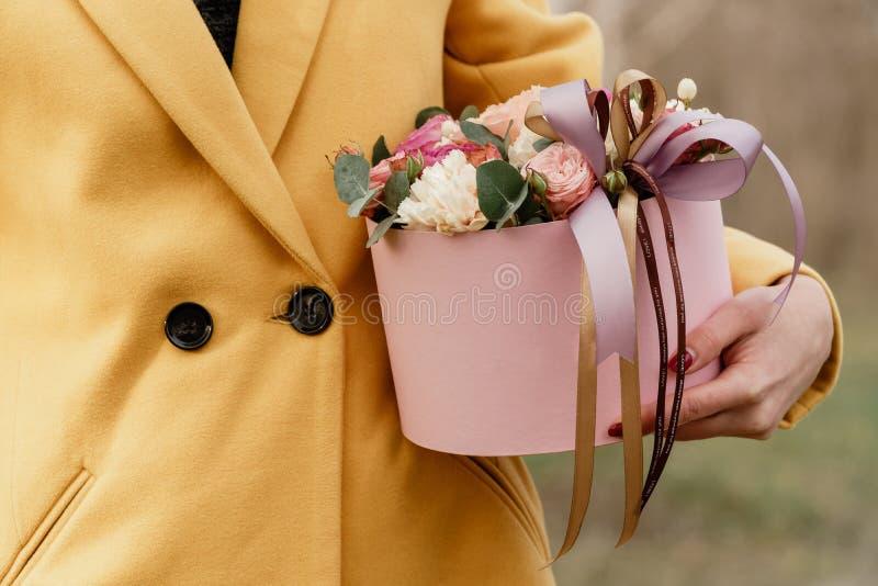 Όμορφη γυναίκα που κρατά το ρόδινο κιβώτιο με τα λουλούδια Δώρο στην ημέρα των γυναικών Floral σχέδιο αντιπροσωπείας, κείμενο θέσ στοκ φωτογραφία