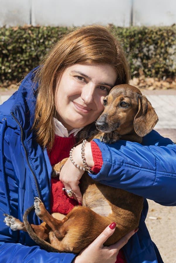 Όμορφη γυναίκα που κρατά το dachshund της στο πάρκο στοκ εικόνα