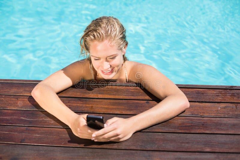 Όμορφη γυναίκα που κλίνει στο poolside και που δακτυλογραφεί ένα μήνυμα κειμένου στοκ εικόνες με δικαίωμα ελεύθερης χρήσης