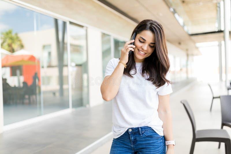 Όμορφη γυναίκα που μιλά στο κινητό τηλέφωνο στη λεωφόρο αγορών στοκ εικόνες
