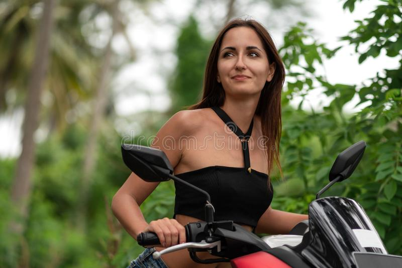 Όμορφη γυναίκα που οδηγεί ένα μηχανικό δίκυκλο και εξετάζει την απόσταση E στοκ εικόνες με δικαίωμα ελεύθερης χρήσης