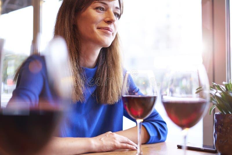 Όμορφη γυναίκα που πίνει το κόκκινο κρασί με τους φίλους στον καφέ, πορτρέτο με το γυαλί κρασιού κοντά στο παράθυρο Διακοπές κλίσ στοκ εικόνες