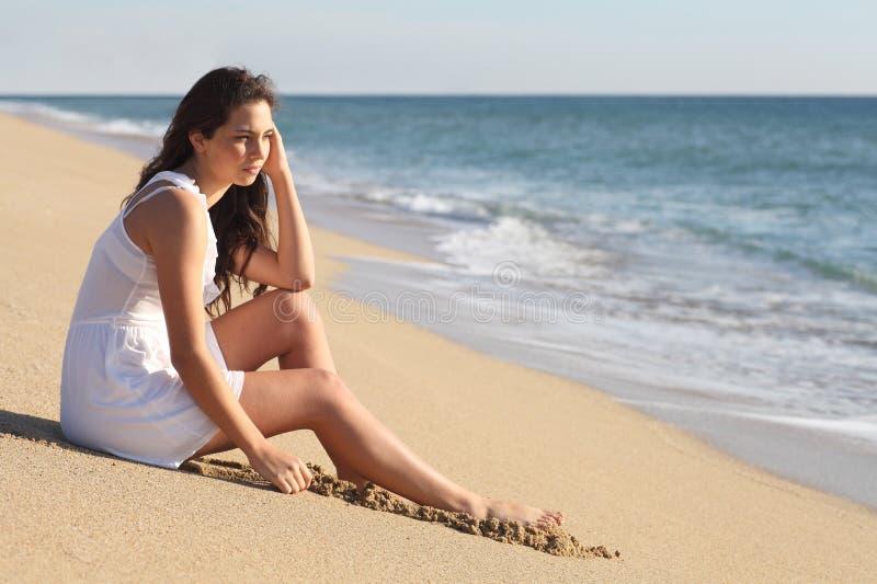 Όμορφη γυναίκα που σκέφτεται και που προσέχει τη θάλασσα στοκ φωτογραφία