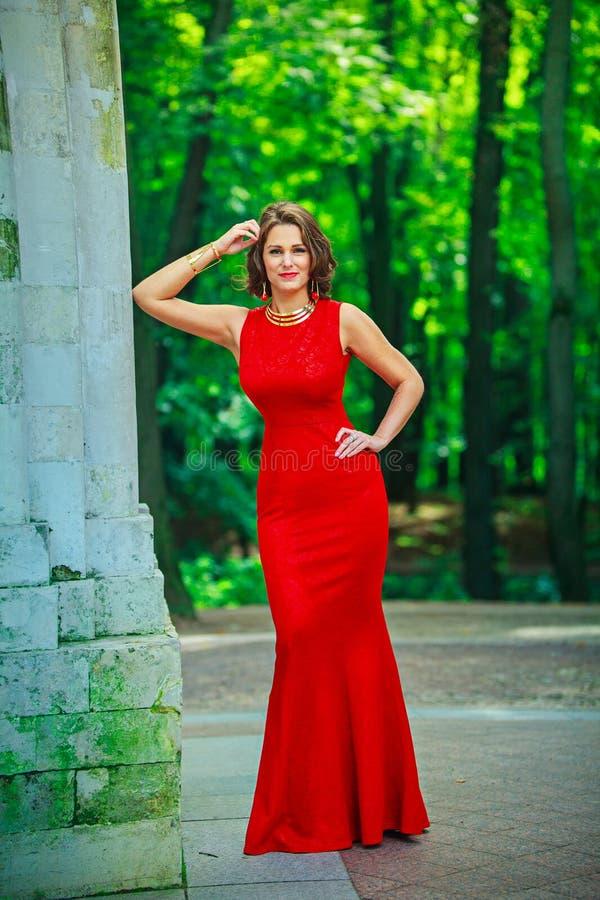 Όμορφη γυναίκα που στέκεται και που χαμογελά στο abeautiful φυσικό backg στοκ φωτογραφίες με δικαίωμα ελεύθερης χρήσης