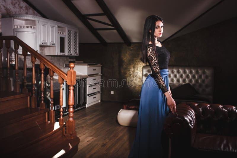 Όμορφη γυναίκα που στέκεται κοντά στον εκλεκτής ποιότητας καναπέ δέρματος στοκ εικόνες με δικαίωμα ελεύθερης χρήσης