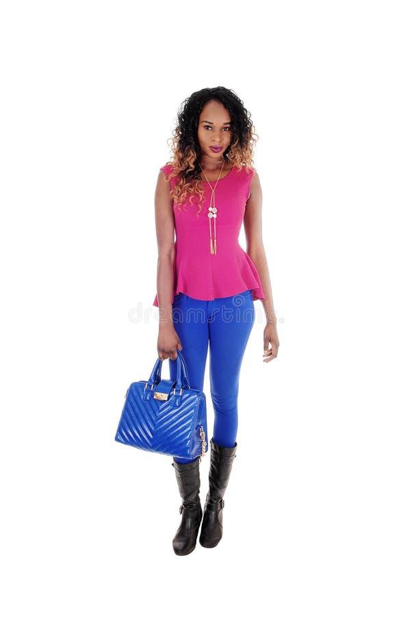 Όμορφη γυναίκα που στέκεται με το μπλε πορτοφόλι στοκ εικόνα