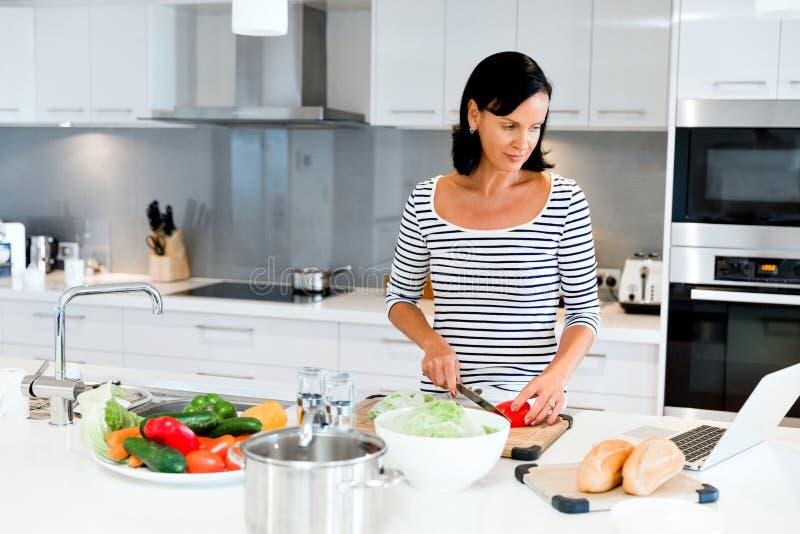 Όμορφη γυναίκα που στέκεται στην κουζίνα και το μαγείρεμα στοκ εικόνες