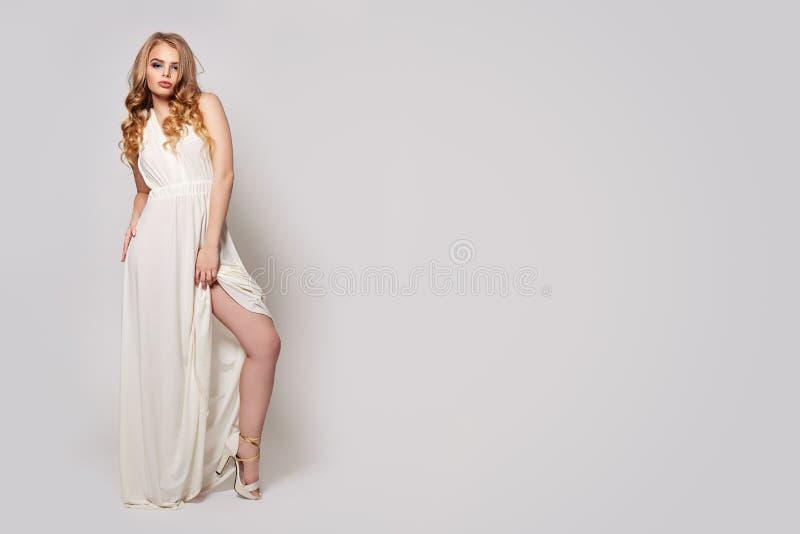 Όμορφη γυναίκα που στέκεται στο άσπρο υπόβαθρο Αρκετά πρότυπο κορίτσι στο φόρεμα βραδιού και πόδια στα υψηλά παπούτσια τακουνιών στοκ εικόνες