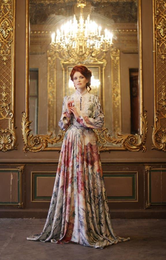 Όμορφη γυναίκα που στέκεται στο δωμάτιο παλατιών με τον καθρέφτη στοκ εικόνες