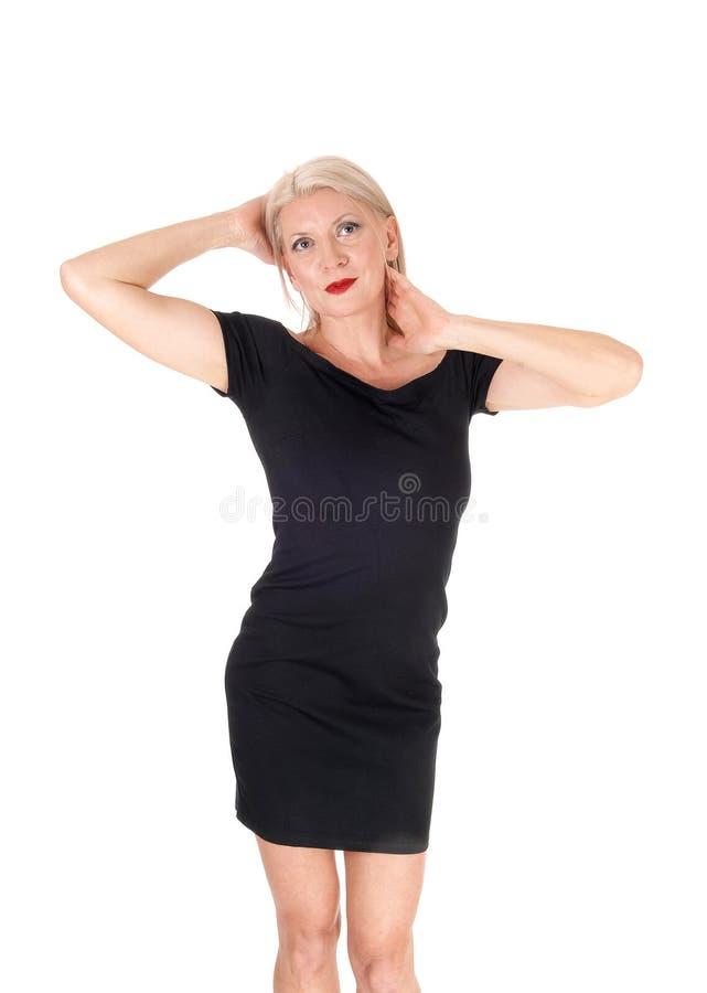 Όμορφη γυναίκα που στέκεται χέρια στα κοντά μαύρα φορεμάτων στο κεφάλι στοκ φωτογραφία με δικαίωμα ελεύθερης χρήσης