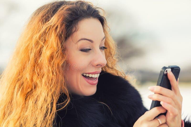 Όμορφη γυναίκα που στέλνει το μήνυμα κειμένου από το κινητό τηλέφωνό της στοκ φωτογραφίες