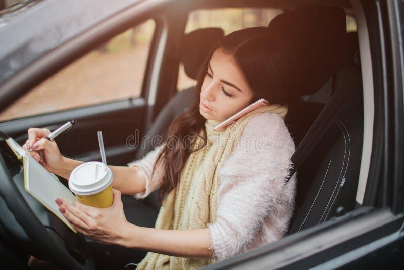 Όμορφη γυναίκα που τρώει τα τρόφιμα και που οδηγεί στο αυτοκίνητό της στοκ εικόνες με δικαίωμα ελεύθερης χρήσης