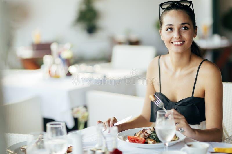 Όμορφη γυναίκα που τρώει το γεύμα στο εστιατόριο στοκ εικόνες