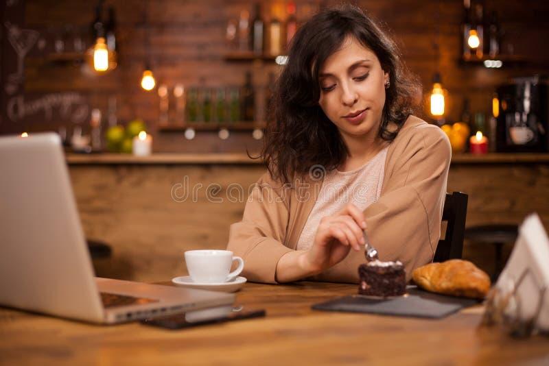 Όμορφη γυναίκα που τρώει το εύγευστο κέικ σοκολάτας σε μια καφετερία στοκ φωτογραφία