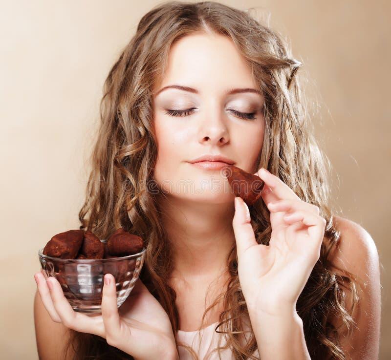Όμορφη γυναίκα που τρώει bonbon σοκολάτας στοκ φωτογραφίες