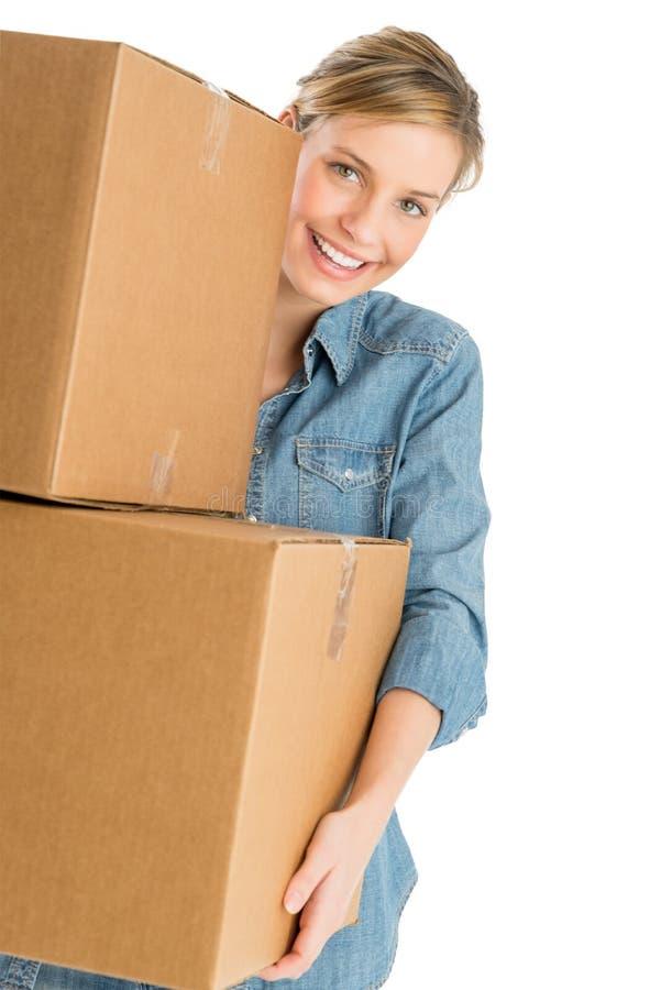 Όμορφη γυναίκα που φέρνει τα συσσωρευμένα κουτιά από χαρτόνι στοκ εικόνες