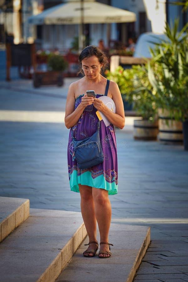 Όμορφη γυναίκα που φαίνεται ένα κινητό τηλέφωνο στην οδό στοκ εικόνα με δικαίωμα ελεύθερης χρήσης