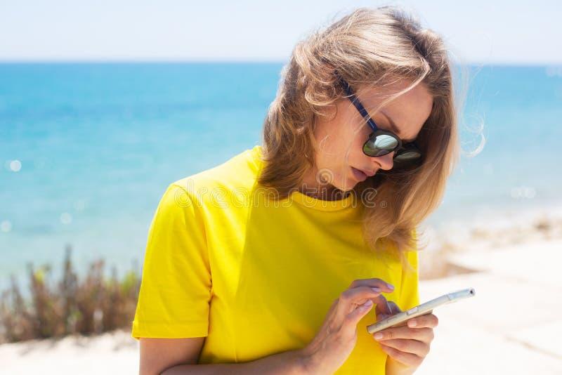 Όμορφη γυναίκα που φορά στην μπλούζα, το τζιν παντελόνι και τα γυαλιά ηλίου, που μένουν κοντά στη γραμμή ακτών Χρησιμοποιεί το κι στοκ εικόνες με δικαίωμα ελεύθερης χρήσης