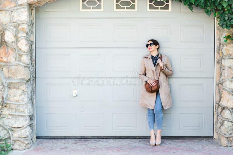 Όμορφη γυναίκα που φορά τα τζιν και την τάφρο, που στέκονται ενάντια στον τοίχο στην οδό πόλεων Η περιστασιακή μόδα, κομψός καθημ στοκ εικόνες