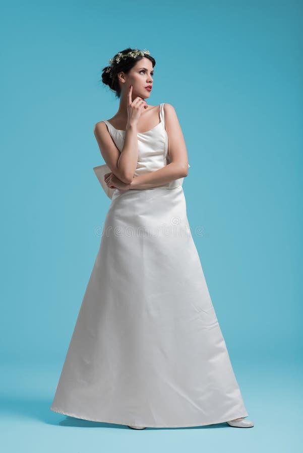 Όμορφη γυναίκα που φορά το γαμήλιο φόρεμα στο κυανό κλίμα στοκ εικόνα