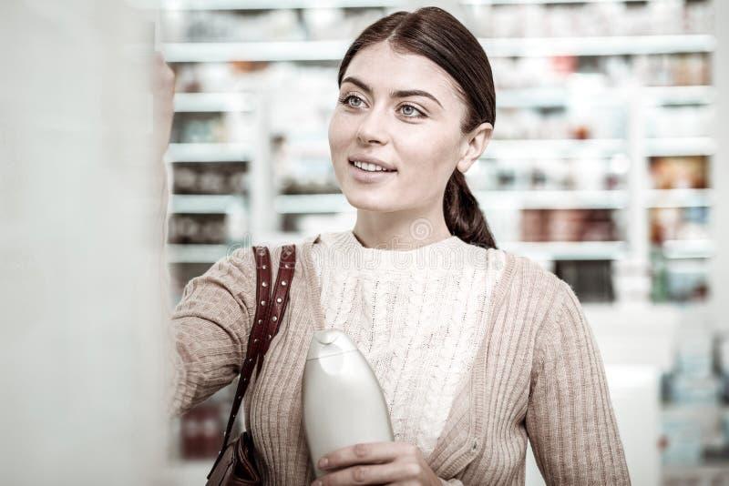 Όμορφη γυναίκα που χαμογελά ψωνίζοντας στο κατάστημα φαρμακείων στο Σαββατοκύριακο στοκ εικόνα
