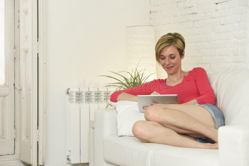 Όμορφη γυναίκα που χαμογελά την ευτυχή εργασία στο σπίτι με το ψηφιακό μαξιλάρι υπολογιστών ταμπλετών στοκ φωτογραφία