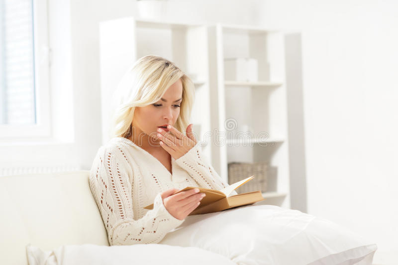 Όμορφη γυναίκα που χασμουριέται διαβάζοντας ένα βιβλίο στοκ φωτογραφία