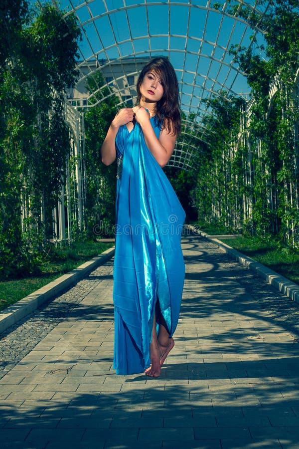 Όμορφη γυναίκα που χορεύει χωρίς παπούτσια σε ένα μακρύ μπλε φόρεμα στοκ εικόνα