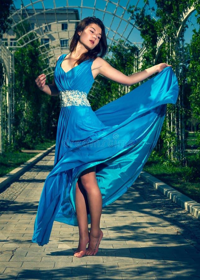 Όμορφη γυναίκα που χορεύει χωρίς παπούτσια σε ένα μακρύ μπλε φόρεμα στοκ εικόνες με δικαίωμα ελεύθερης χρήσης