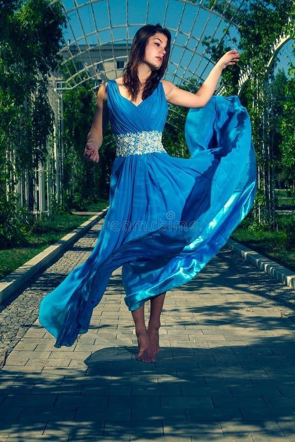 Όμορφη γυναίκα που χορεύει χωρίς παπούτσια σε ένα μακρύ μπλε φόρεμα στοκ φωτογραφία