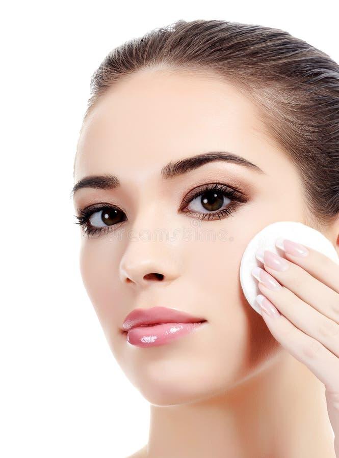 Όμορφη γυναίκα που χρησιμοποιεί ένα μαξιλάρι βαμβακιού για να αφαιρέσει το makeup της στοκ εικόνα