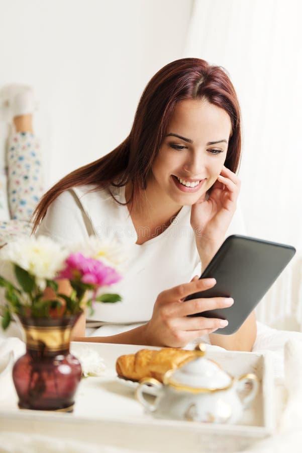 Όμορφη γυναίκα που χρησιμοποιεί μια ταμπλέτα σε ένα δωμάτιο με το πρόγευμα στο κρεβάτι στοκ εικόνες
