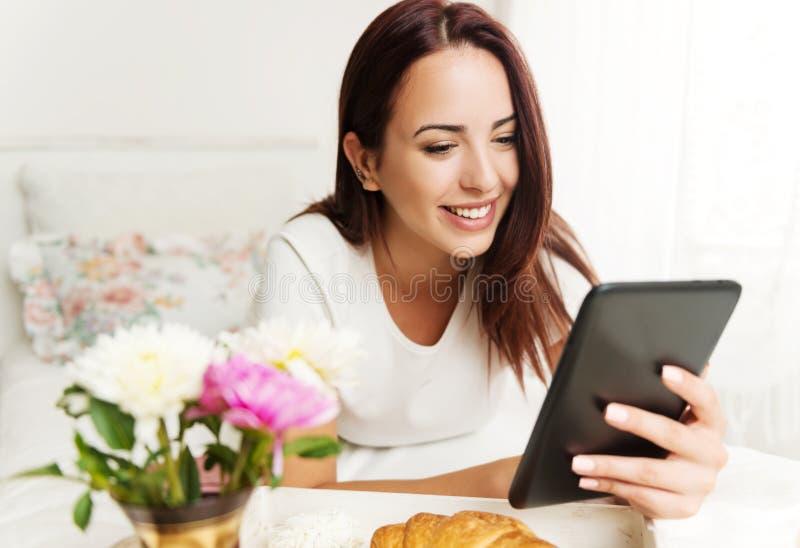 Όμορφη γυναίκα που χρησιμοποιεί μια ταμπλέτα σε ένα δωμάτιο με το πρόγευμα στο κρεβάτι στοκ εικόνες με δικαίωμα ελεύθερης χρήσης