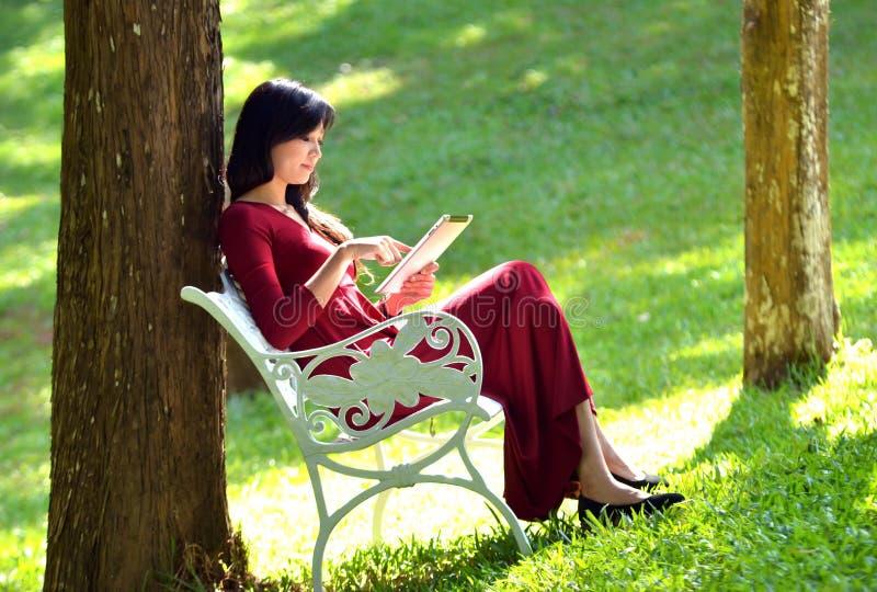 Όμορφη γυναίκα που χρησιμοποιεί την ταμπλέτα στοκ εικόνες
