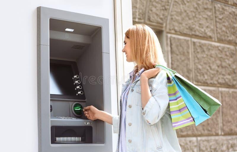 Όμορφη γυναίκα που χρησιμοποιεί τη μηχανή μετρητών για τα χρήματα withdrawall στοκ εικόνα