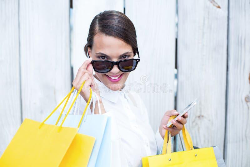 Όμορφη γυναίκα που χρησιμοποιεί τις τσάντες αγορών εκμετάλλευσης smartphone της στοκ φωτογραφίες