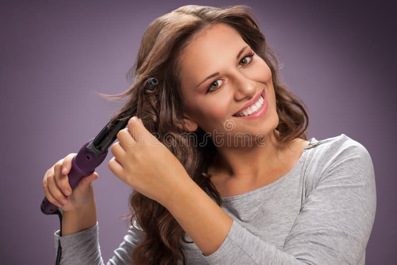 Όμορφη γυναίκα που χρησιμοποιεί τον κατσαρώνοντας σίδηρο στην κυματιστή τρίχα της στοκ φωτογραφίες