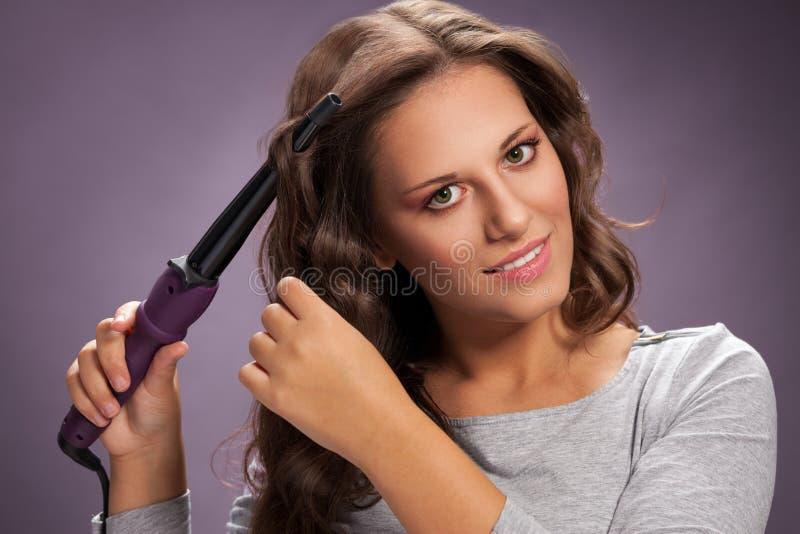Όμορφη γυναίκα που χρησιμοποιεί τον κατσαρώνοντας σίδηρο στοκ φωτογραφία με δικαίωμα ελεύθερης χρήσης