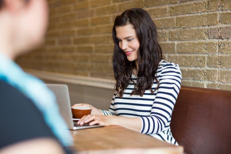 Όμορφη γυναίκα που χρησιμοποιεί το lap-top στην καφετέρια στοκ φωτογραφίες