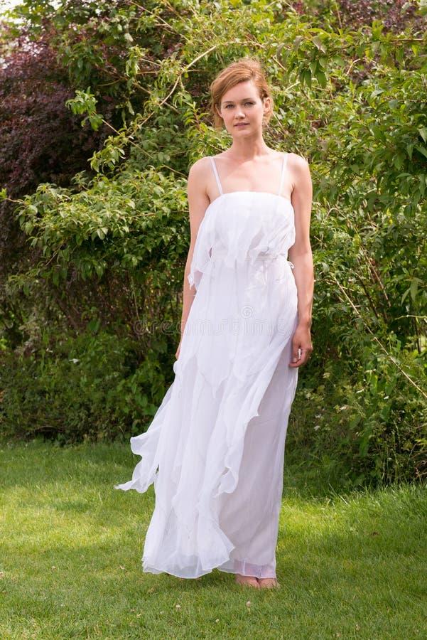 Όμορφη γυναίκα σε ένα άσπρο φόρεμα που στέκεται χωρίς παπούτσια στη χλόη στοκ εικόνες