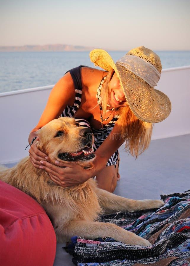 Όμορφη γυναίκα σε ένα καπέλο με το συμπαθητικό σκυλί του Λαμπραντόρ σε ένα γιοτ με το τοπίο θάλασσας στοκ εικόνα με δικαίωμα ελεύθερης χρήσης