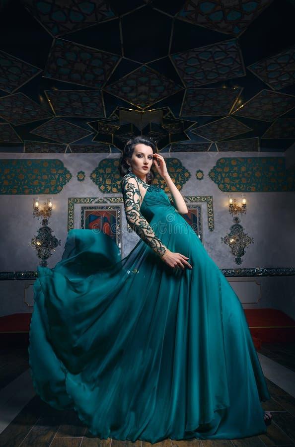 Όμορφη γυναίκα σε ένα πράσινο μακρύ φόρεμα σε ένα υπόβαθρο πλουσιοπάροχα στοκ εικόνες