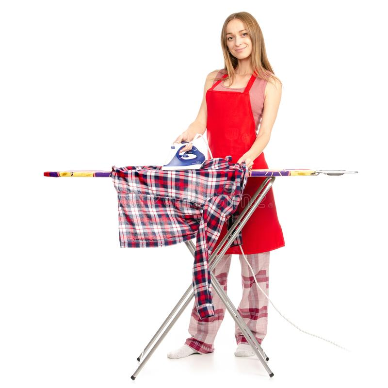 Όμορφη γυναίκα σε μια ποδιά που σιδερώνει ένα πουκάμισο στο σιδερώνοντας πίνακα με έναν σίδηρο στοκ εικόνες
